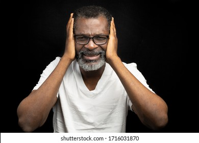 A man in pain is holding his head in his two hand
