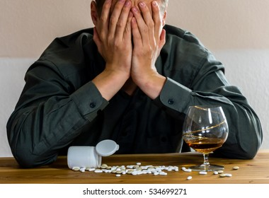 Man in pain with pills and alcohol