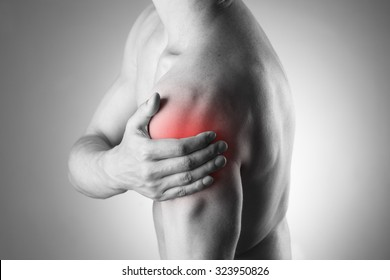 Man with pain in shoulder. Pain in the human body. Black and white photo with red dot