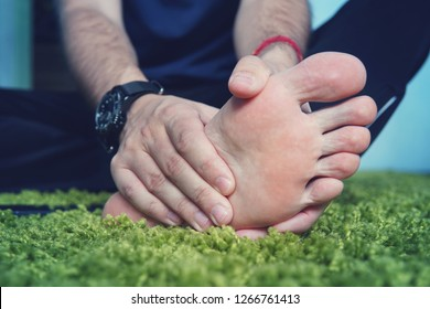 Man with painful and inflamed gout on his foot around the big toe area. Man's hand being massaged a foot