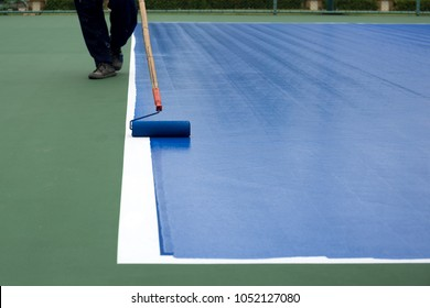 Man painter use paint roller painting tennis court in blue color