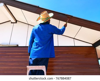 A man is painting brown color to the wood surface