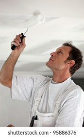Man painting ceiling white