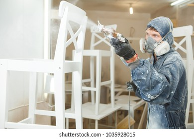 Man painting chair into white paint in respiratory mask. Application of flame retardant ensuring fire protection, airless spraying.