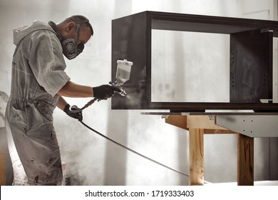 Man Painting Furniture Details.  Painter with safety mask painting a wooden furniture with spray gun.