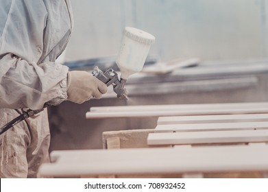 Man painting furniture details. Worker using spray gun. The carpenter paints furniture details in white color in the carpentry shop. close