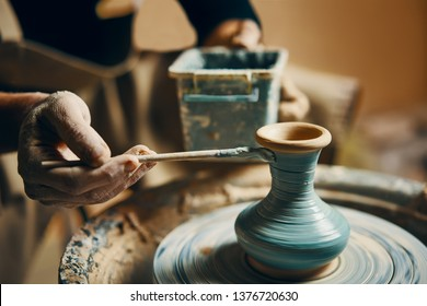 Man painting handmade pottery at ceramic workshop. Art concept