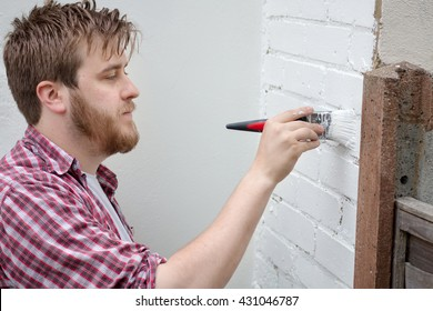 Man painting house wall with brush. DIY Home Improvement.