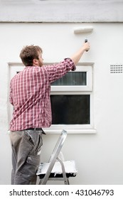 Man painting house wall on stepladder with paint roller. DIY Home Improvement.