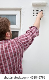 Man painting house wall with paint roller. DIY Home Improvement.