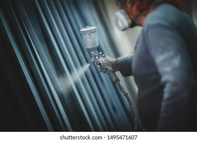 Man painting metal products with a spray gun