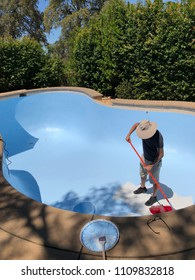Man painting pool interior