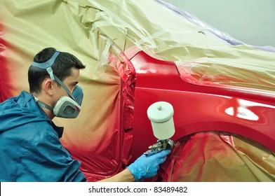 Man painting a red car.