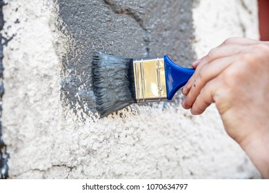 Man is painting and renewing a stone wall with grey paint, hand and brush in the front