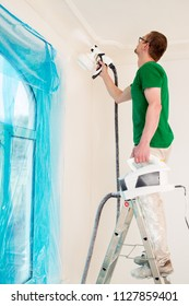 Man painting room walls with paint spray gun while standing on ladder.