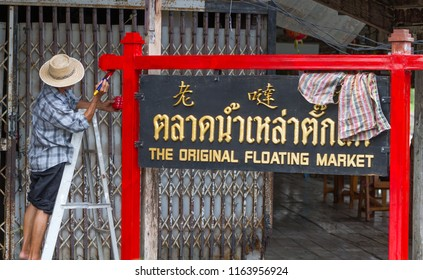 """Man painting sign """"The original floating market"""", sign written in chinese, thai and english languages at Damnoen Saduak floating market in Thailand"""