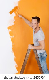 Man is painting a wall with orange color