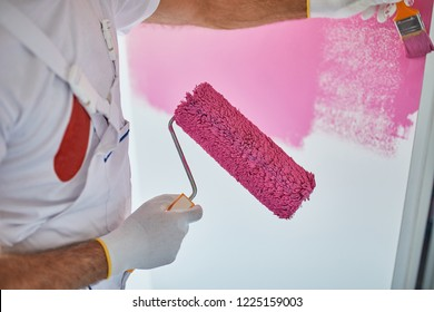 Man Painting The Wall With Paint Brush.