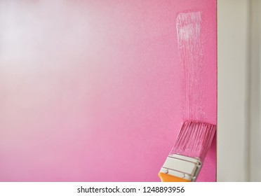 Man Painting The Wall With Paint Brush