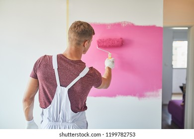 Man Painting The Wall With Paint Roller