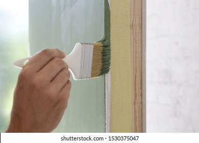 Man painting a wall with a paintbrush with green color, DIY house improvement project