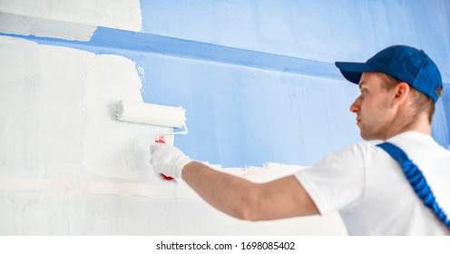 Man painting wall with roller. Builder worker painting walls with white color.