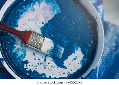 Man painting wall with roller. Man using paint roller while working indoors.