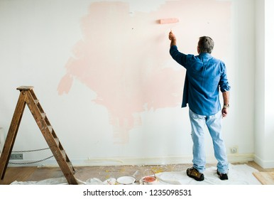 Man painting the walls pink