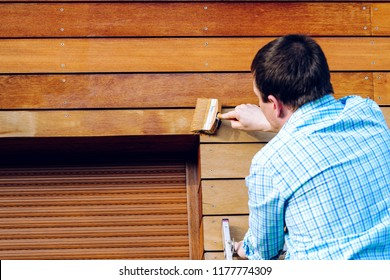 Man painting wooden wall with a brush- painting woodwork outside