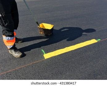 Man painting the yellow line on the concrete floor at car park on sunny day