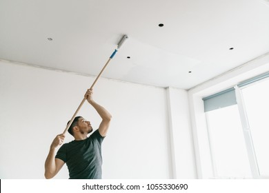 the man paints the ceiling in a gray color with a roller in a bright room. Repair and painting.