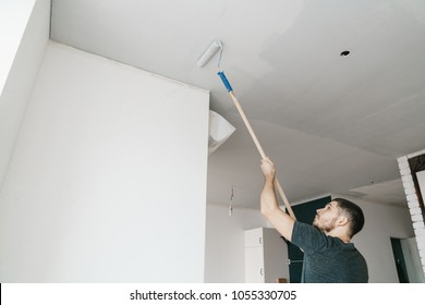 the man paints the ceiling in a gray color roller at home. Repair and renovation of the apartment.