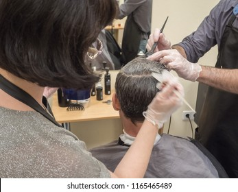 A man paints his hair in a Barber shop. Innovative technologies of hair restoration for men.