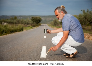 Man paints the line of the road