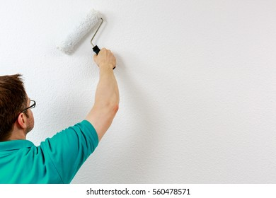 Man paints wall in white, close up