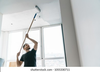 The man paints the walls and the ceiling in gray on his balcony in the backlight. Painting and repair in the room.