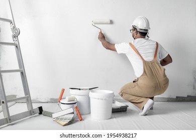a man paints a white wall with a roller. Repair of the interior. Young male decorator painting a wall in the empty room, concept builder or painter in helmet with paint roller over the empty room.