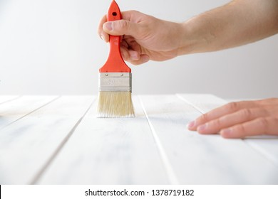 A man paints a wooden board with white paint. The concept of DIY and renovation of new things. A man tinkering at home, working with wood.