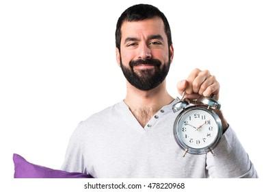 Man in pajamas holding vintage clock