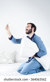Man with Pajamas on Bed Taking a Selfie with a Smartphone