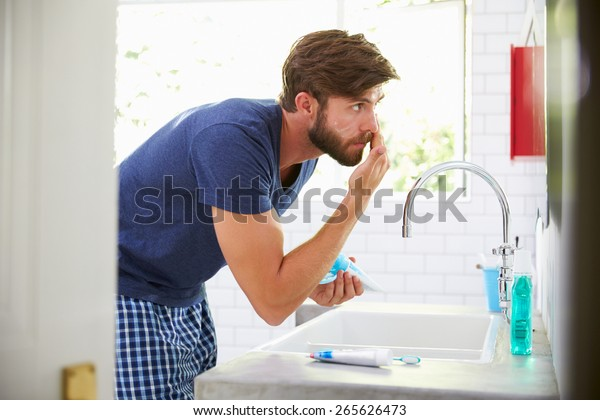 Man In Pajamas Putting On Moisturizer In Bathroom