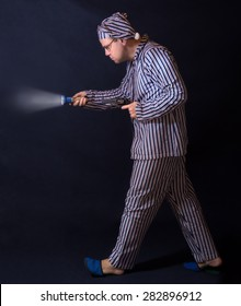Man in pajamas walking around with a gun. The man in the striped pajamas goes with a pistol on a dark background. Night Watch in pajamas. Armed man in pajamas lit a hand-held torch.