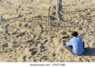 The man in the Panama hat and sailor suit sits on the sand beach, brick coal and Barbecuing in the summer at a picnic one.
