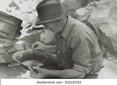 Man panning gold at Pinos Altos, New Mexico. He holds a gold nugget. May-June, 1940. Photo by Russell Lee. 13_236)