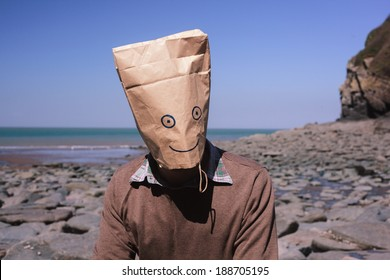 Man with a paperbag over his head is sitting on the beach