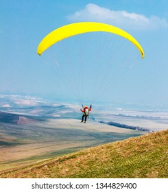 Man with a paraglider against the sky