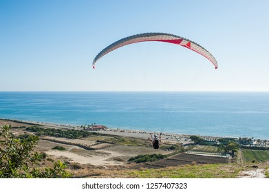 Man paragliding above fields with scenic sea view at Cyprus