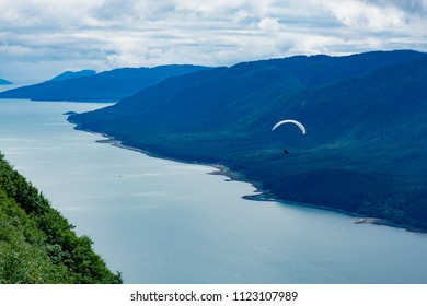 Man paragliding in along the Alaska Coast