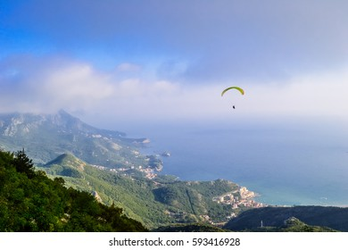 Man paragliding over Budva mountains overseeing sunny seaside