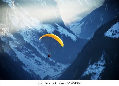 Man paragliding over mountains